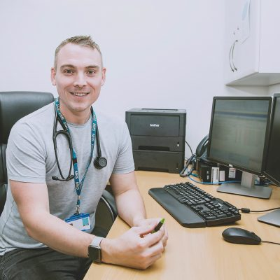 james-alexander-male-gp-at-desk