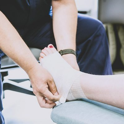 Nurse wrapping foot in bandage in Urgent Care Centre