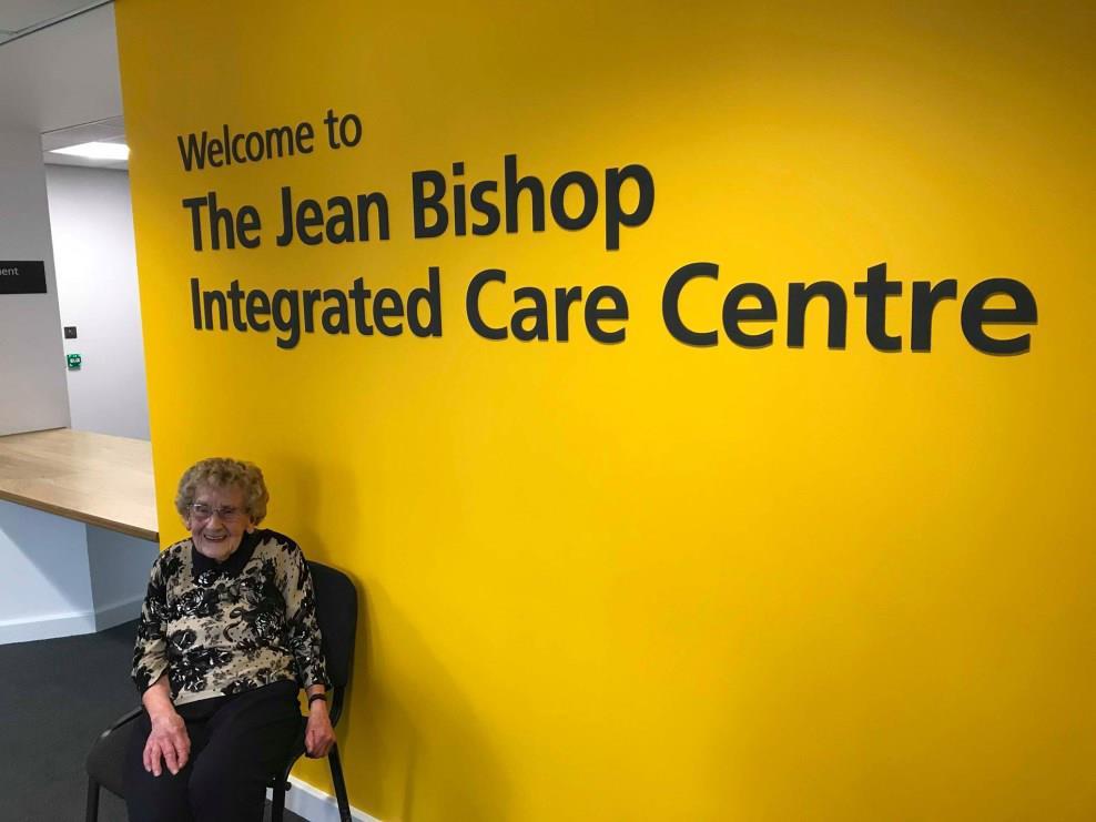 Older woman sat near care centre sign